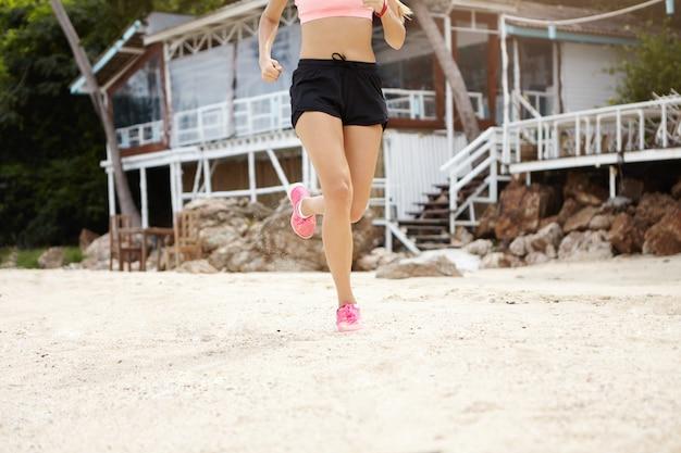 Fitness und sport. stilvoller weiblicher läufer in der sportbekleidung, die cardio-training am strand macht. beschnittene ansicht der sportlerin, die schwarze shorts und rosa turnschuhe trägt, die auf sand laufen