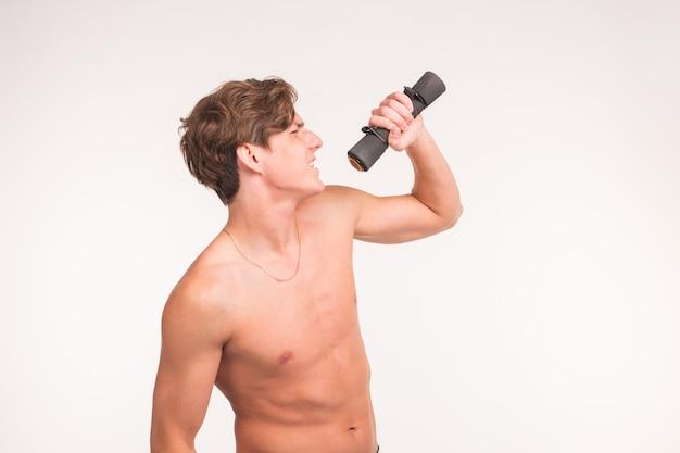 Fitness-, witz- und people-konzept - porträt eines gutaussehenden athletischen mannes, der mit hantel auf weißem hintergrund singt.