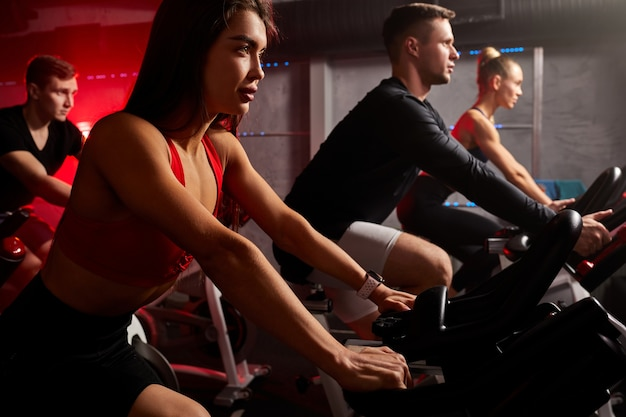 Fitness zusammen auf fahrrädern. junge freunde treten auf einem stationären fahrrad im fitnessstudio im rot neonbeleuchteten raum in die pedale. cardio-übungen am gerät