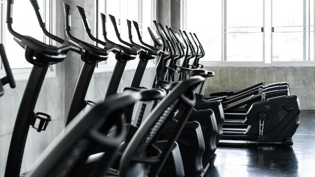 Fitnesscenter und moderne geräte für das training im fitnessraum. ellipsentrainer in einer reihe. konzept von büro, arbeitsplatz und stadion.