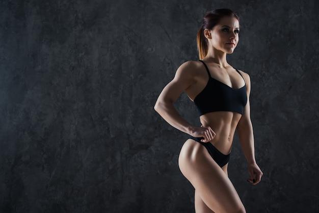 Fitnessfrau an einer dunklen wand