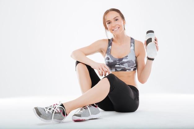 Fitnessfrau auf dem boden mit wasser im studio