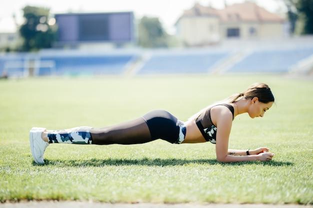 Fitnessfrau auf stadionplanking auf grünem gras