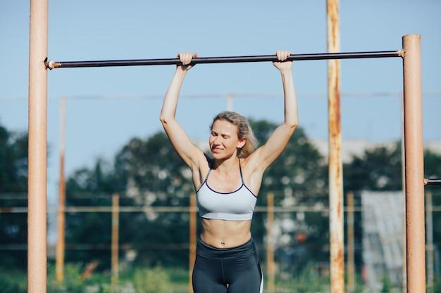 Fitnessfrau, die auf einem drehkreuz festzieht
