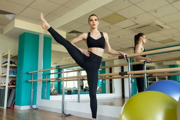 Fitnessfrau, die ausfallschritte übungen für beinmuskeltraining macht. aktives mädchen, das vorne ein bein schritt longe übung für hintern macht.
