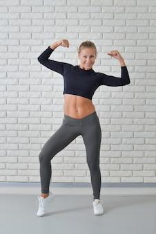Fitnessfrau, die den bizeps gegen weiße backsteinmauer in der turnhalle zeigt, porträt in voller länge.