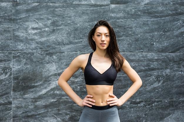 Fitnessfrau, die draußen steht und lächelt. porträt der sportlichen frau, die gegen eine wand steht.