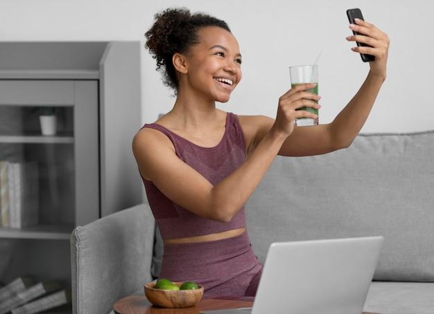 Fitnessfrau, die ein selfie nimmt, während sie einen fruchtsaft hat