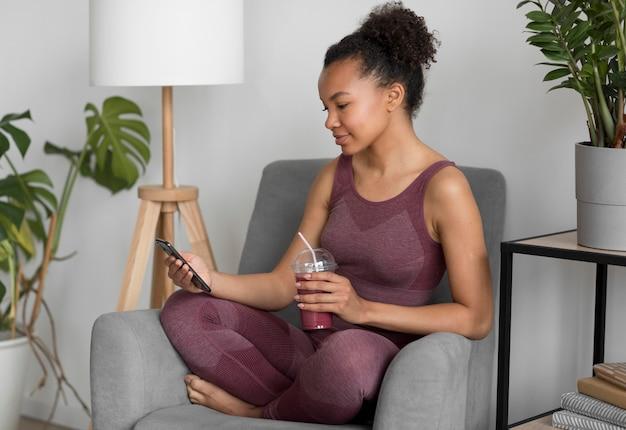 Fitnessfrau, die einen entgiftungssaft beim verwenden eines smartphones hat