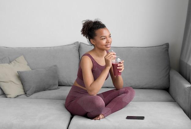 Fitnessfrau, die einen entgiftungssaft zu hause hat