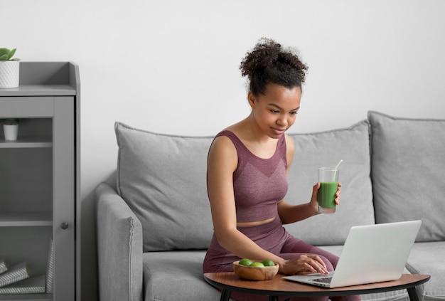 Fitnessfrau, die einen fruchtsaft beim verwenden eines laptops hat