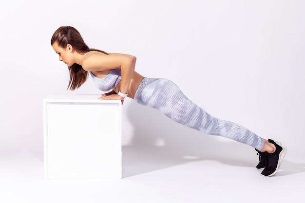 Fitnessfrau, die liegestütze macht oder in plankenpose steht, aufpumpt und die muskeln stärkt