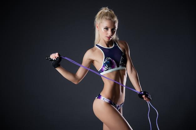 Fitnessfrau, die mit springseil auf einem schwarzen hintergrund aufwirft. sportliche motivation. perfekte weibliche figur. sexy mädchen im studio.