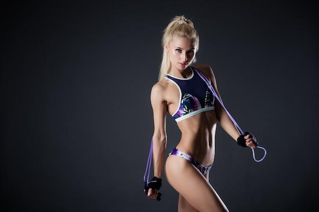 Fitnessfrau, die mit springseil auf einem schwarzen hintergrund aufwirft. sportliche motivation. perfekte weibliche figur.