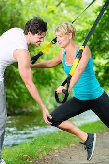 Fitnessfrau, die mit suspensionstrainer und persönlichem sporttrainer im stadtpark unter sommerbäumen trainiert