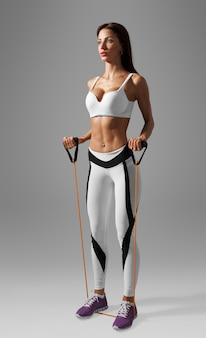 Fitnessfrau, die trainingsübungen für hände und rücken mit expander macht
