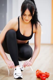 Fitnessfrau, die turnschuhe seil, sportbekleidung und modethema bindet