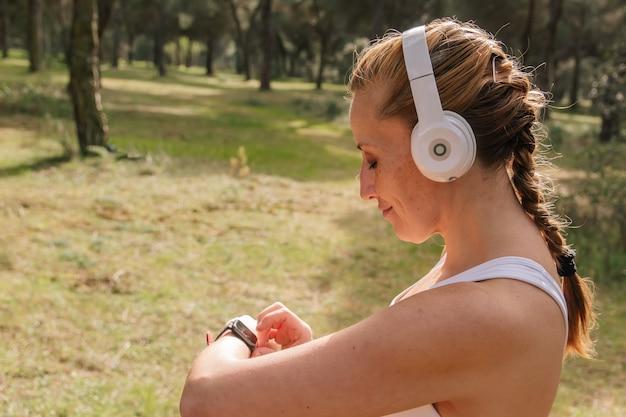 Fitnessfrau, die vor dem training eine intelligente uhr einstellt. fitness- und lifestyle-konzept.