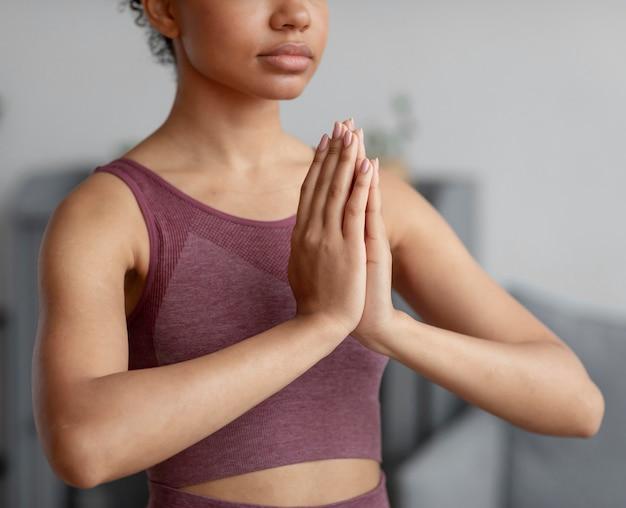 Fitnessfrau, die yoga auf einer yogamatte zu hause tut