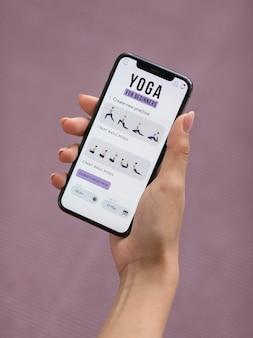 Fitnessfrau, die yoga mit einer mobilen app tut