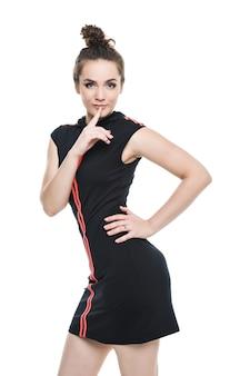 Fitnessfrau im sportstil, der gegen weißen hintergrund steht. isoliert