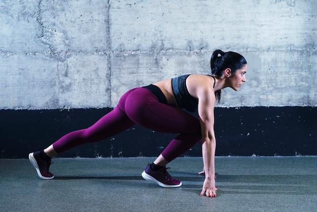 Fitnessfrau in niedriger position bereit für sprintlauf