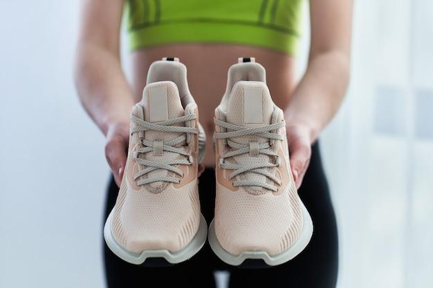 Fitnessfrau in sportbekleidung hält turnschuhe zum laufen. sport treiben und fit sein. sportler mit gesundem sportlichem lebensstil