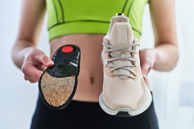 Fitnessfrau in sportbekleidung mit weichen orthopädischen einlegesohlen und turnschuhen zum laufen. behandlung und vorbeugung von plattfüßen und fußkrankheiten, unterstützung des fußgewölbes. fußkomfort. sport bequeme schuhe tragen