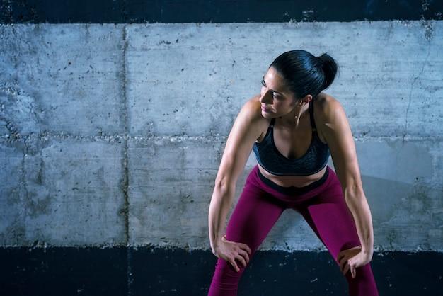 Fitnessfrau in sportkleidung, die sich auf betonwand stützt und beiseite schaut