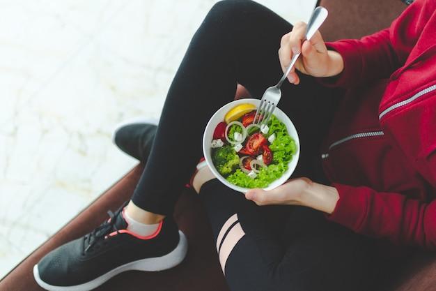 Fitnessfrau in turnschuhen und sportbekleidung ruht sich aus und isst nach dem training einen gesunden, frischen salat. gesundes lebensstilkonzept.