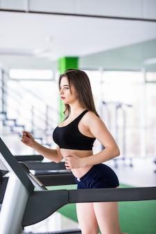 Fitnessfrau läuft auf sportsimulator im modernen fitnesscenter, gekleidet in schwarzer sportbekleidung