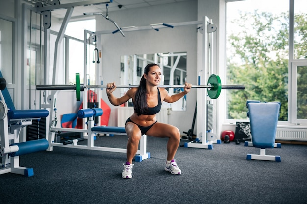 Fitnessfrau macht kniebeugen mit langhantel.