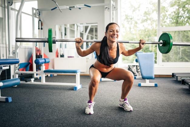 Fitnessfrau macht kniebeugen mit langhantel