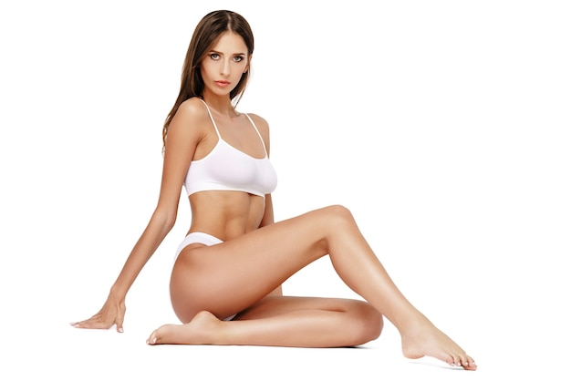 Fitnessfrau mit einem schönen körper auf weißem hintergrund