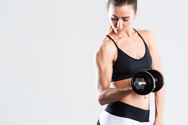 Fitnessfrau mit einem schönen körper, der übungen mit hanteln isoliert tut. gesunder lebensstil.