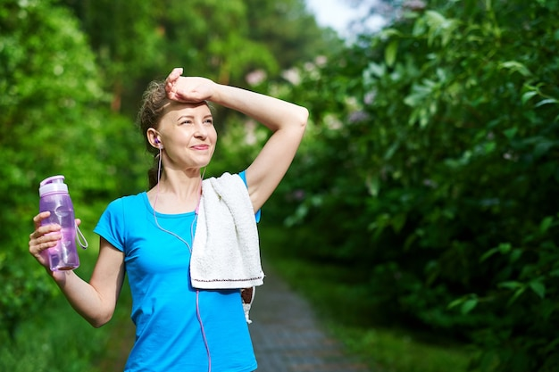 Fitnessfrau mit flasche und handtuch wasser nach dem lauftraining im sommerpark