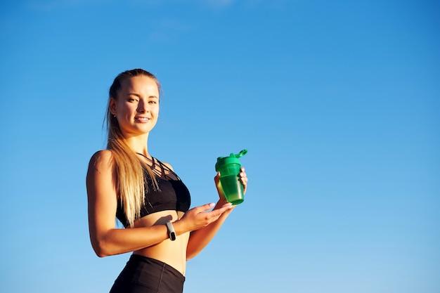 Fitnessfrau mit flasche wasser nach dem laufenden training auf blauem himmelhintergrund
