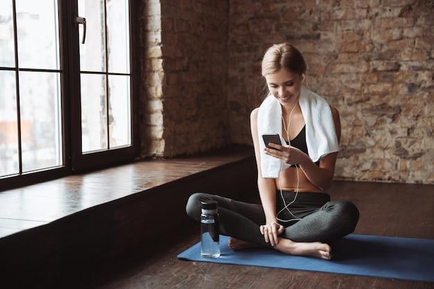 Fitnessfrau mit handtuch, das im fitnessstudio sitzt, während telefon verwendet wird