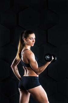 Fitnessfrau mit hanteln, die eine übung auf dunkelheit tun