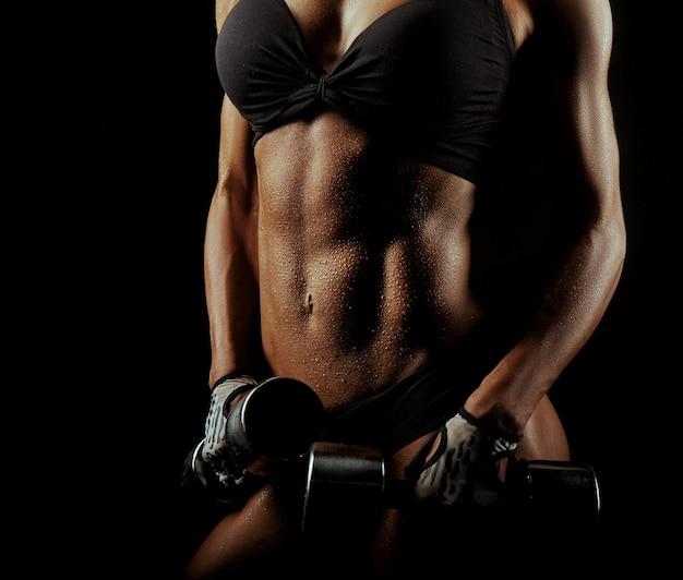 Fitnessfrau mit perfektem körper, der hanteln hält