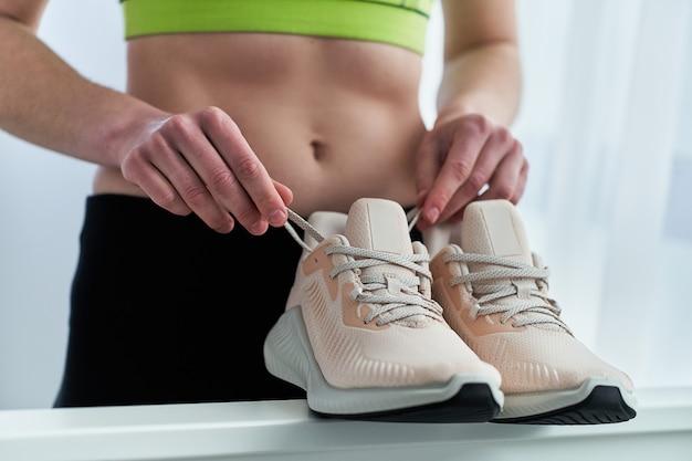 Fitnessfrau mit schmaler passform, die sportbekleidung trägt, hält beige turnschuhe zum joggen und laufen. sport treiben und fit sein. sportler mit gesundem sportlichem lebensstil