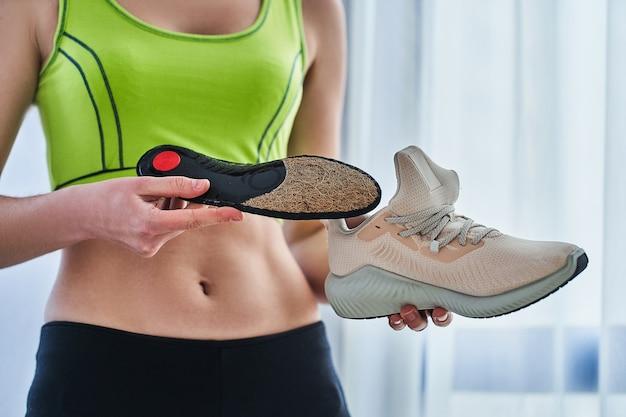 Fitnessfrau mit weichen orthopädischen einlegesohlen und turnschuhen für das lauftraining. behandlung und vorbeugung von plattfüßen und fußkrankheiten, unterstützung des fußgewölbes. fußkomfort. sport bequeme schuhe tragen