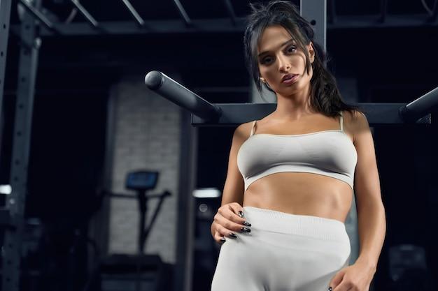 Fitnessfrau posiert im fitnessstudio