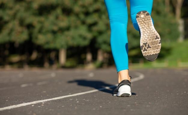 Fitnessfrauenfüße während des lauftrainingszuges auf dem stadion. platz für text