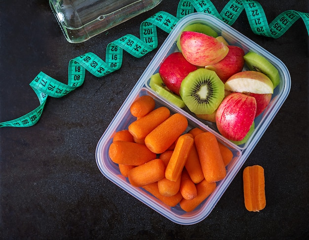 Fitnessgeräte. gesundes essen. konzept gesunde ernährung und sport lebensstil. vegetarisches mittagessen. dummkopf, wasser, früchte auf schwarzer tabelle. . flach liegen