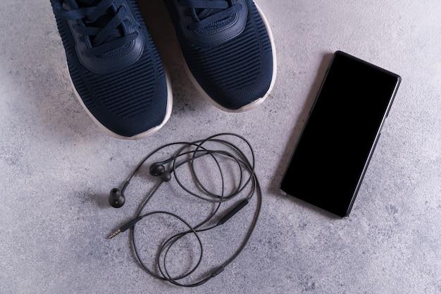 Fitnessgeräte mit turnschuhen, smartphone und kopfhörern auf grau