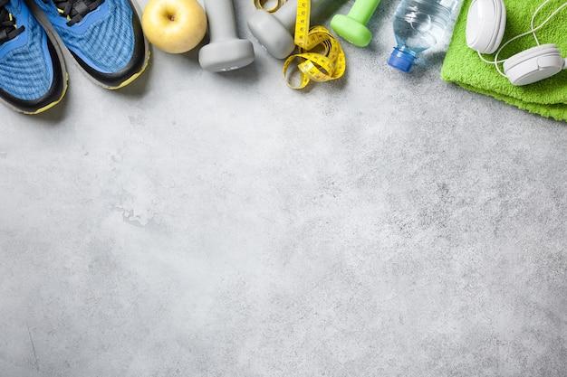 Fitnesshintergrund mit hanteln, turnschuhen, handtuch, kopfhörern und wasserflasche