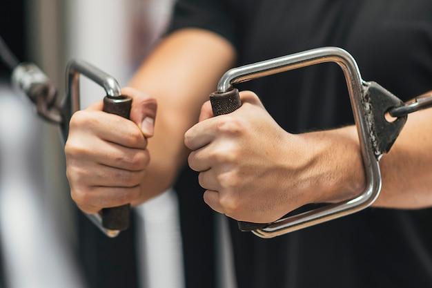 Fitnessjunge zieht riemenscheiben im fitnessstudio