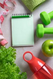 Fitnesskonzept hintergrund mit hanteln wasserflasche apfelsalat handtuch und maßband