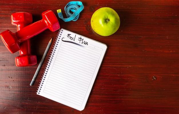 Fitnesskonzept mit gesundem ernährungsplan. fitnessgeräte und gesundes essen. flatlay-kopierraum